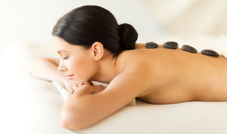 Female Client lying on Stomach with Hot Stone placed on back
