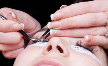 Client getting eyelash extensions put onto eyes
