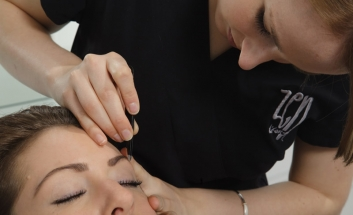 Girl getting her eyebrows plucked by therapist